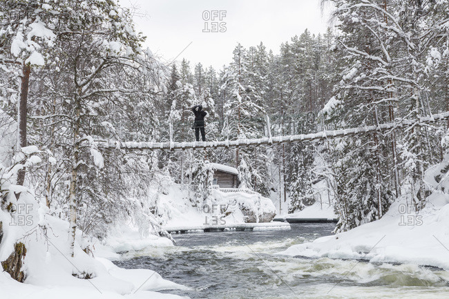 Person taking a picture from a bridge above the Myllykoski rapids, Finland