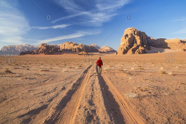 Man walking on the tracks in the desert, Wadi Rum, Jordan