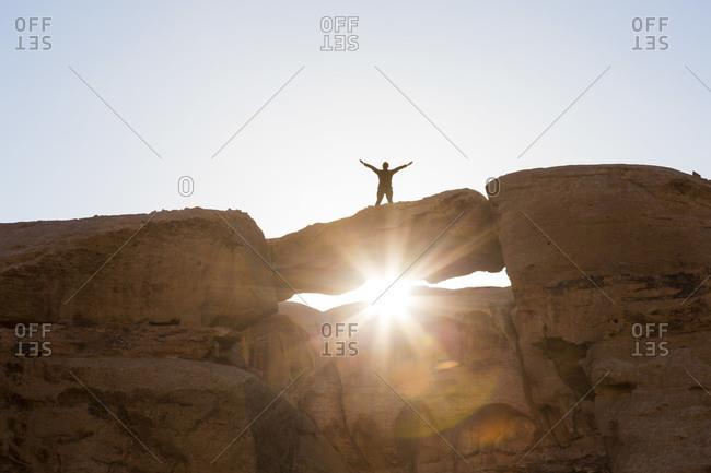Woman standing on a natural desert archway, Wadi Rum, Jordan
