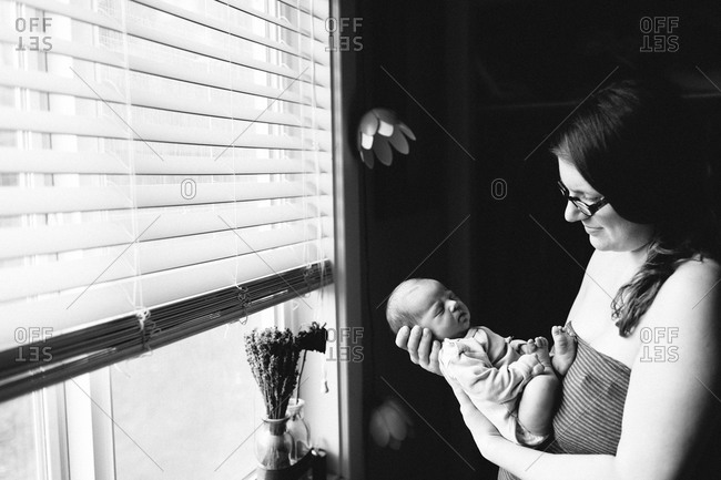 Woman holding a baby at a window