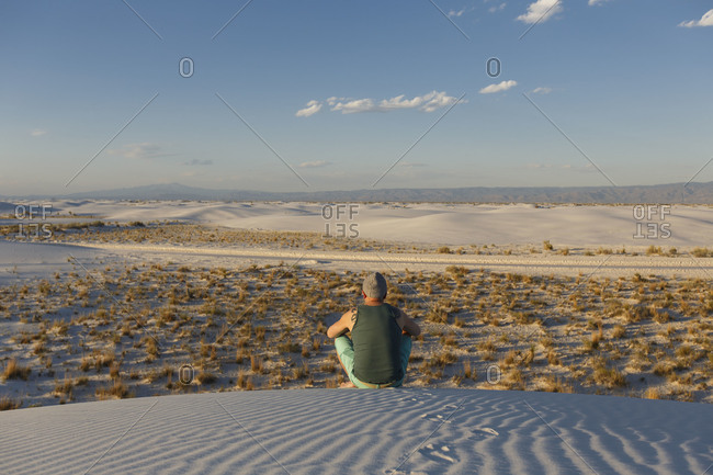 A man looks out over scrubland from atop a desert sand dune, New Mexico