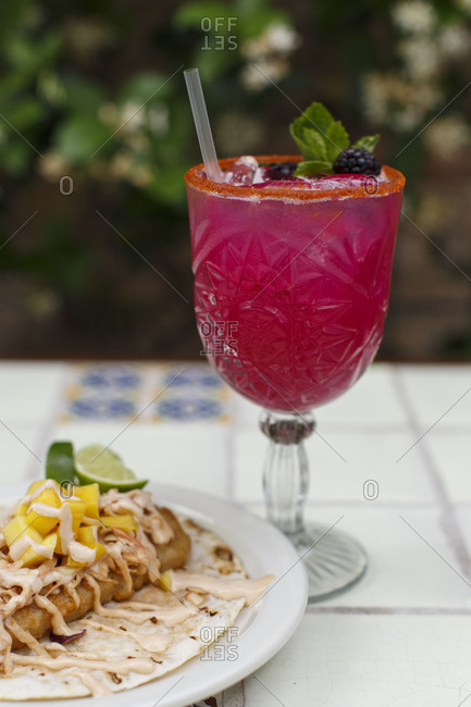 Magenta cocktail beside taco meal