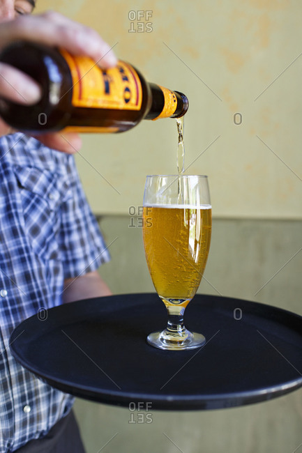 Waiter pouring lager into glass
