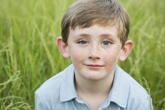 Boy in a blue shirt with brown hair and freckles