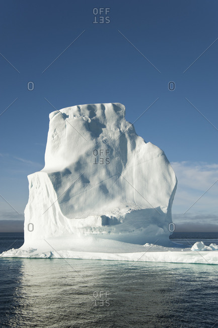 A tall iceberg on the waters of the shore of Greenland