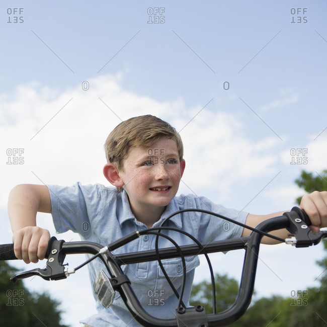 Young boy leaning over the handlebars of a bicycle