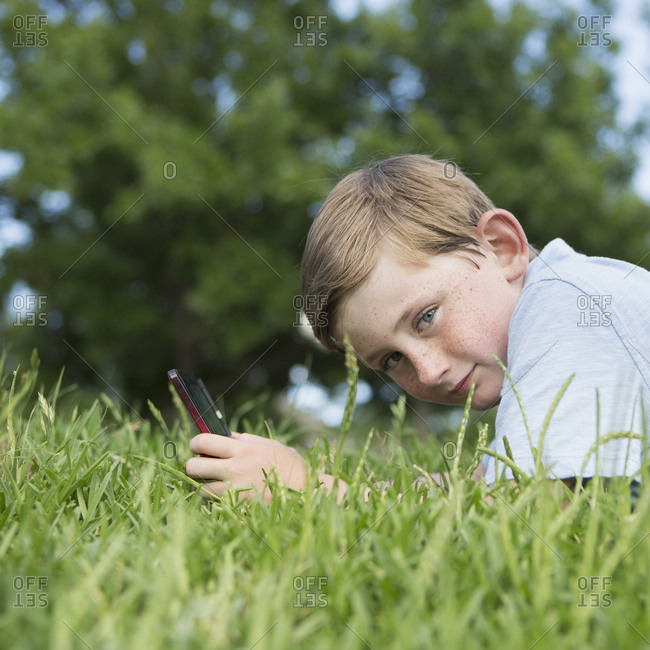 Young boy sitting on the grass using a hand held electronic games device