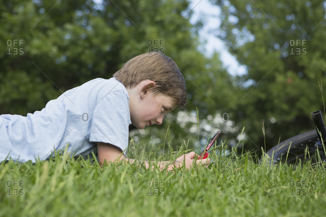 Young boy lying on the grass playing a hand held electronic game