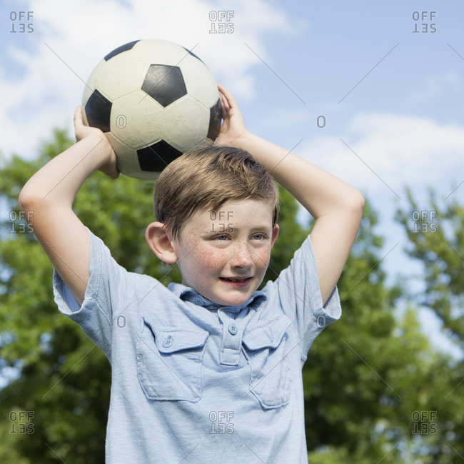 Young boy holding a soccer ball above his head