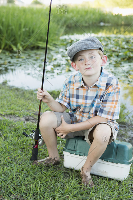 Young boy with his fishing road by a lake or river