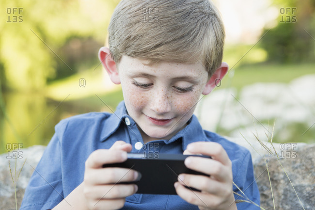 Young boy outdoors sitting leaning against a rock using a handheld electronic game