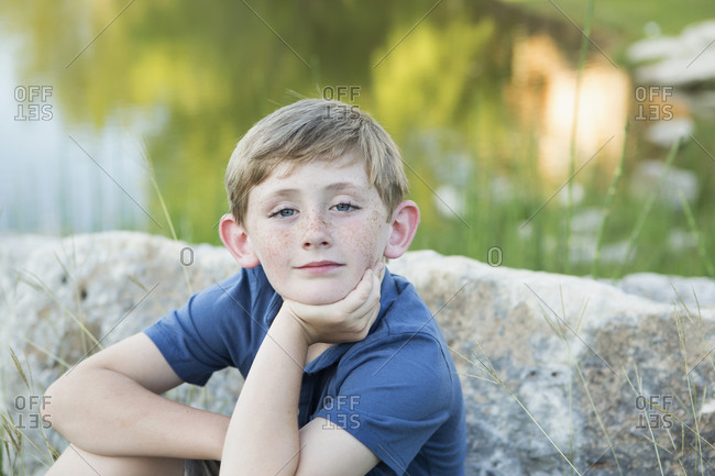 Head and shoulders portrait of a young boy sitting with his chin resting on his hand