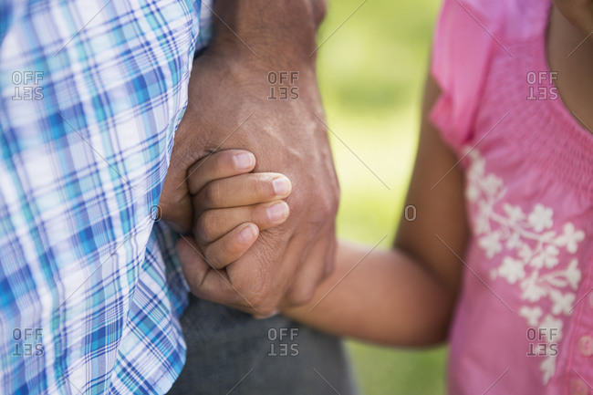 Close up of a father holding his daughter's hand