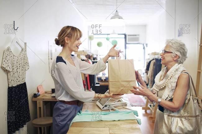 Shop assistant serving an elderly customer in boutique