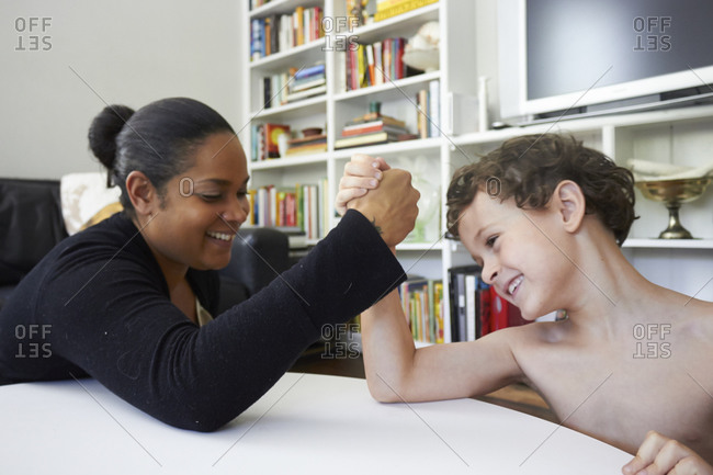 Woman and boy arm wrestling
