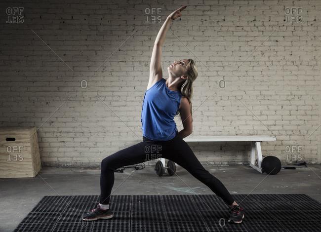 Blonde woman making asana at gym