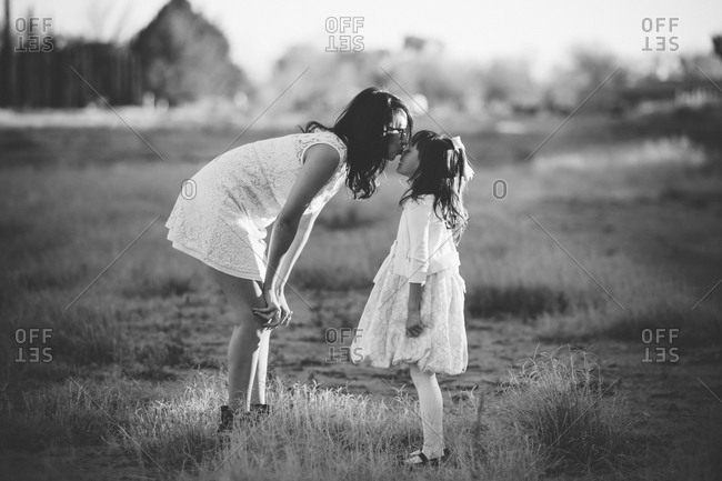 Mother bending over to kiss daughter in a field