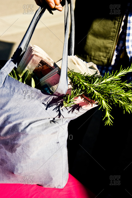 Canvas tote bag full of herbs and newspapers