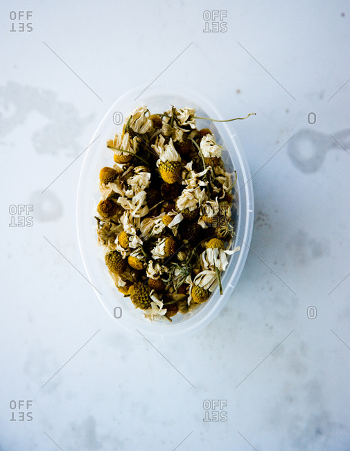 Dried chamomile in plastic container