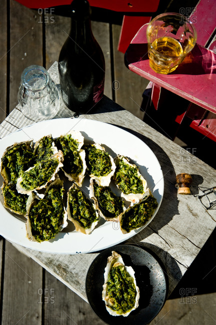 Prepared oysters rockefeller on oval-shape plate