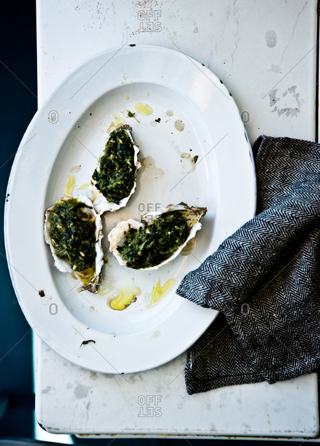 Three oysters rockefeller on plate