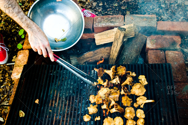 Man grilling freshly cut golden chanterelle