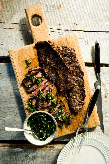 Grilled skirt steak with herb salsa verde on a cutting board