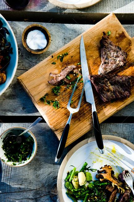 Sliced skirt steak with herb salsa verde on a cutting board
