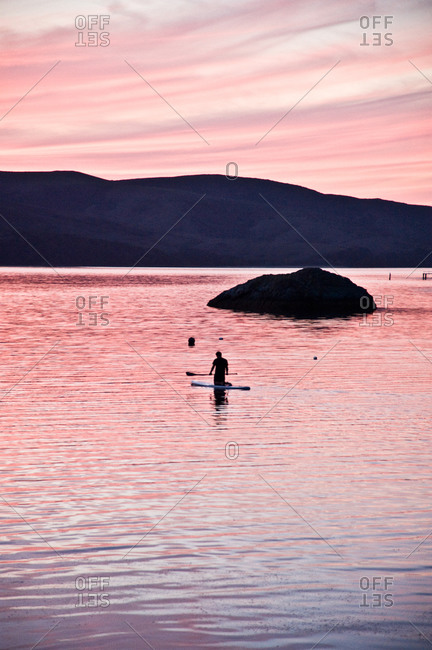 Person paddle boarding at sunset in Tomales Bay