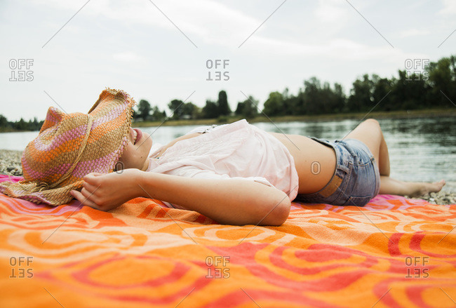 Young woman wearing summer hat relaxing on beach towel
