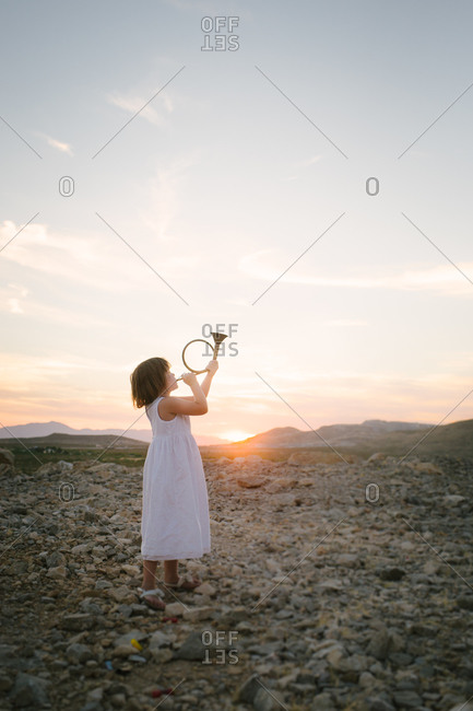 Young girl playing hunting horn at sundown