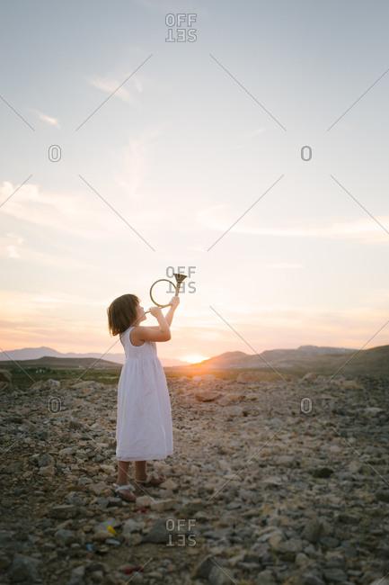 Young girl playing hunting horn at sundown