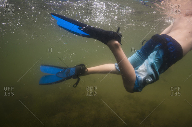 Low section view of a boy swimming in fins