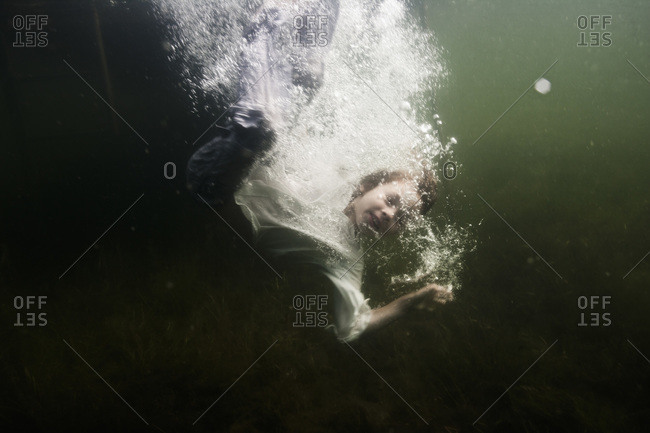 Boy jumping into the sea in clothes