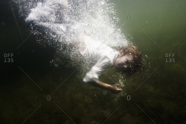 Smiling boy jumping into the water