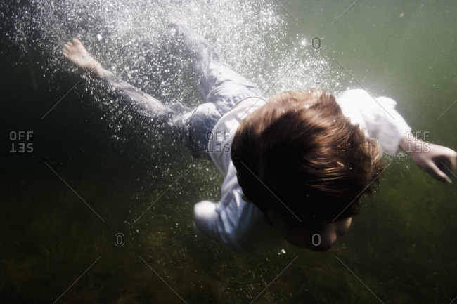 Boy in clothes diving in the sea