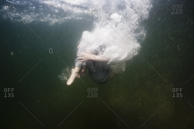 Side view of boy jumping into the sea