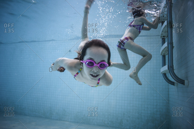 Underwater shot of two girls playing in swimming pool