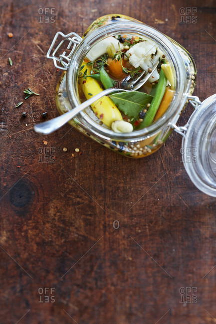 Jar of pickled vegetable relish with green beans, carrots, cauliflower, thyme, bay leaf, peppercorns and white onions in vinegar