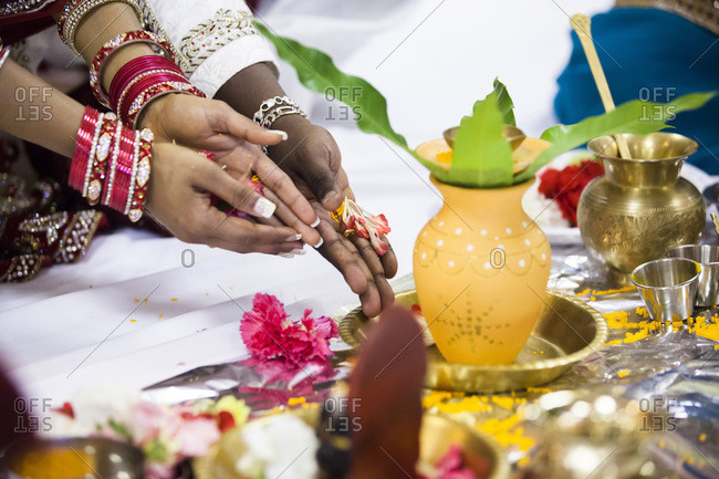 Close-up of bride and groom's hands at Hindu wedding ceremony, Toronto, Ontario, Canada