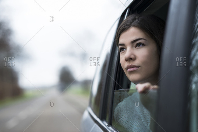 Portrait of young woman sitting inside car looking out the window day dreaming