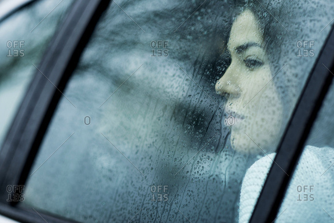 Young woman in car on rainy day, Mannheim, Baden-Wurttemberg, Germany
