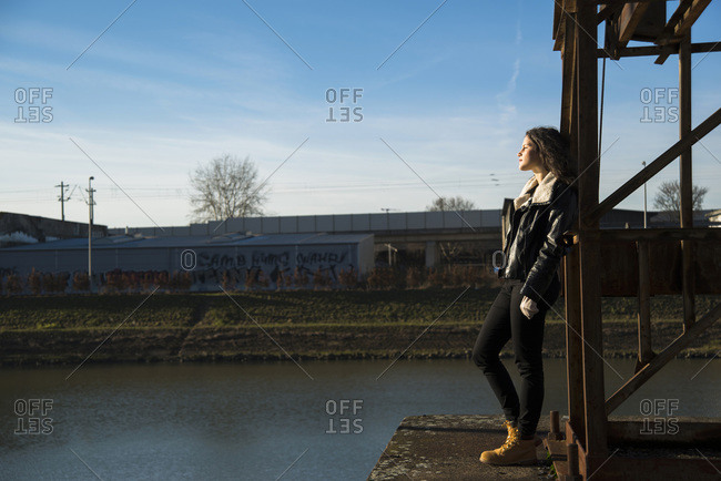 Teenage girl standing on commercial dock outdoors, looking into the distance, Germany