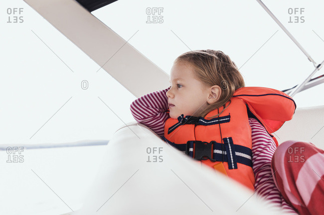 Close-up of 3 year old girl in orange life jacket on a motorboat, Sweden