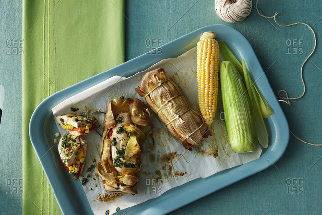 Barbequed chicken breast stuffed with red peppers and herbs with corn wrapped in husk on tray