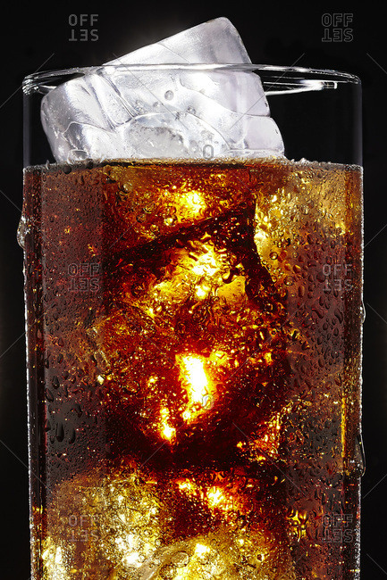 Glass of soda with ice cubes on black background