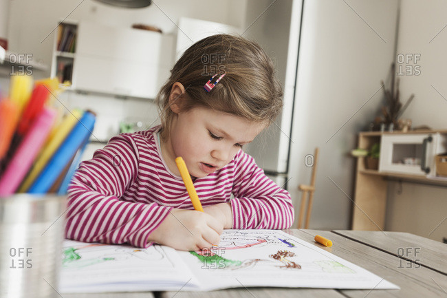 Girl sitting at table and coloring pictures