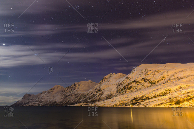Starry night sky with moon illuminating snow covered mountains at a fjord in the Arctic, Norway