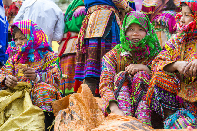 Bac Ha, Vietnam - April 6, 2014: Flower Hmong tribes people sitting at Sunday market, Bac Ha, Vietnam