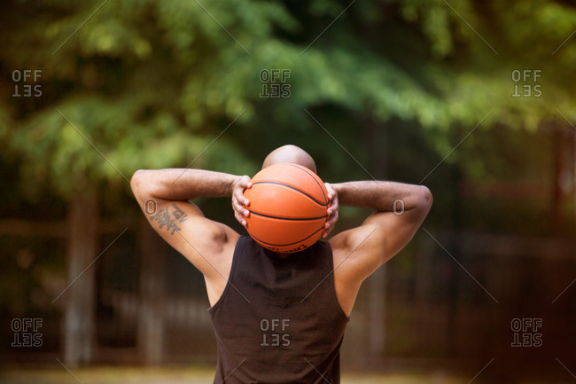 Athletic man holding basketball behind his head with both hands